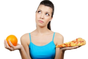 beautiful young woman choosing between pizza and orange
